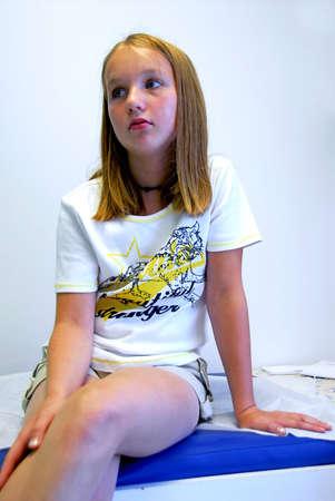 Muchacha joven que espera en la oficina del doctor Foto de archivo - 482915