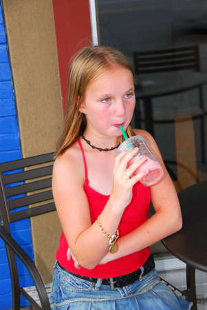 Young girl sitting in outside cafe and drinking a cool refreshing beverage on a hot summer day