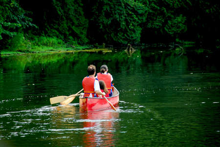 Family of three canoing on a calm green river Stock Photo