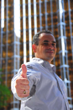 Confident businessman showing thumbs up, focus on a hand 版權商用圖片