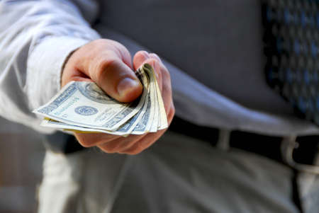 Hand of a businessman offering money photo