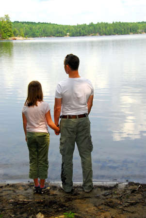 Father and daughter standing on the lake shore and looking at calm water Stock Photo - 496189