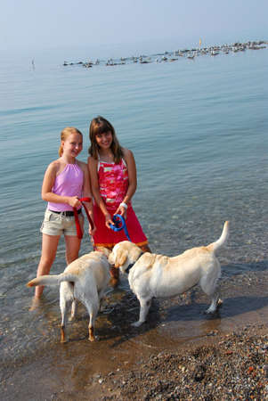 Two girls playing with dogs on a beach photo