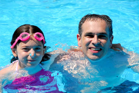 Father and daughter having fun in a swimming pool photo