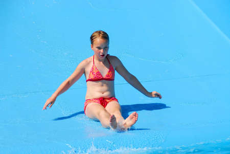 pool preteen: Young girl goind down water slide Stock Photo