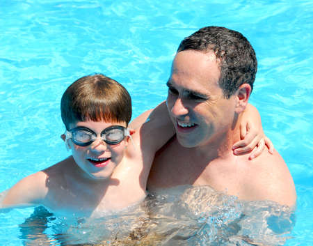 Father and son having fun in a swimming pool photo