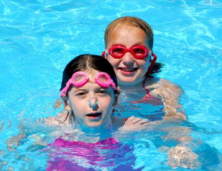 pool preteen: Two girls having fun in a swimming pool