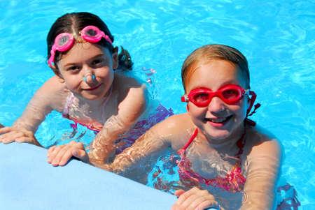 preteen girl: Two girls having fun in a swimming pool