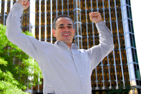 triumphant: Triumphant businessman in the city raising arms in victory