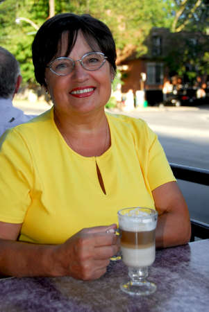 Smiling mature woman in outdoor cafe holding a coffee Stock Photo - 502668