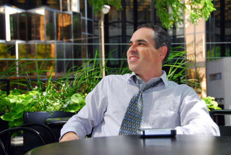 Businessman relaxing in outdoor cafe after work photo