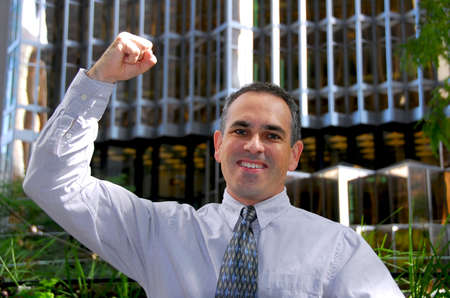triumphant: Triumphant businessman in the city raising an arm in victory Stock Photo