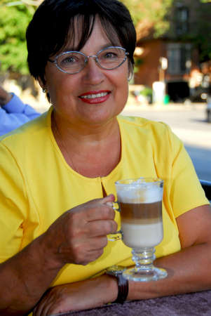 Happy mature woman in outdoor cafe holding a coffee Stock Photo - 510608
