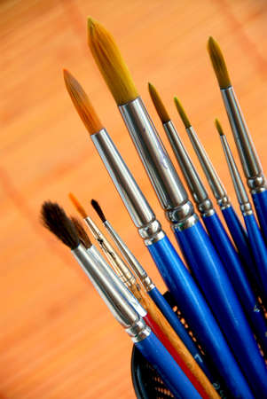 Paintbrushes in a metal mesh holder photo