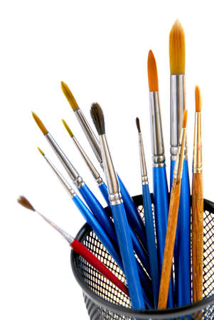 Paintbrushes in a metal mesh holder on white background photo