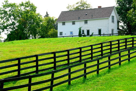 ranching: Farmhouse with fence among green fields