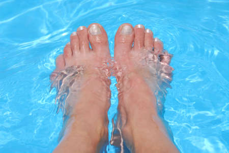 Womans feet cooling in clear blue water
