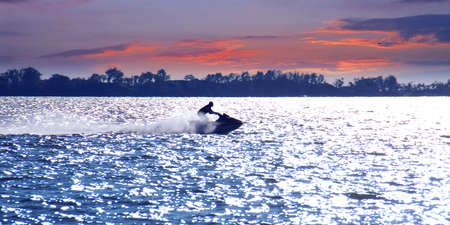 Man on jet ski at sunset