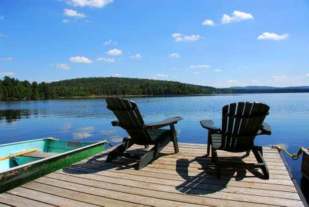 silla de madera: Dos sillas de madera Adirondack en dique frente a un lago azul con nubes reflexiones  Foto de archivo