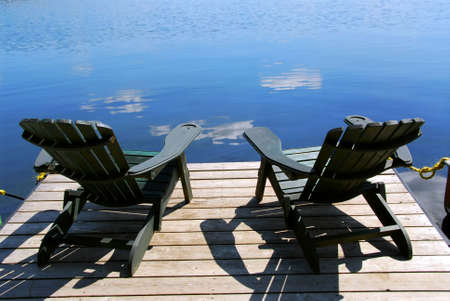 Two adirondack wooden chairs on dock facing a blue lake with clouds reflections photo