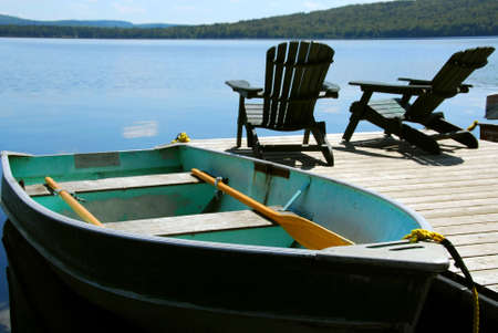pier: Paddle boat and two adirondack wooden chairs on dock facing a blue lake Stock Photo