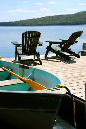 chairs: Paddle boat and two adirondack wooden chairs on dock facing a blue lake Stock Photo