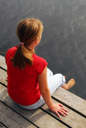 edge: Young girl dipping feet in the lake from a wooden boat dock