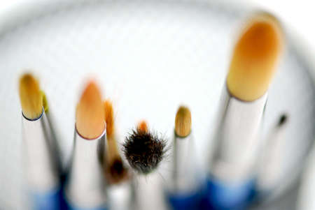 Macro of paintbrushes on white background top view photo