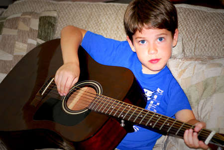 child singing: Young boy playing a guitar