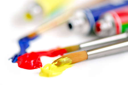 smeared: Macro of paintbrushes and paint tubes of primary colors