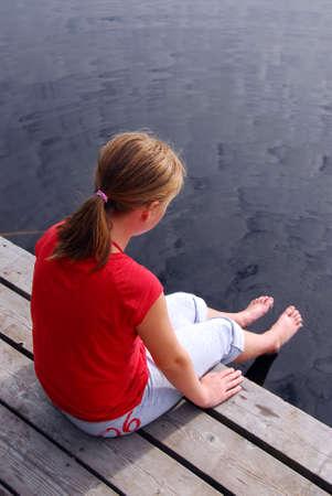 530380-ni-a-sentada-en-el-borde-del-muelle-barco-se-sumerge-sus-pies-en-el-agua.jpg?ver=6