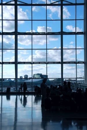 People waiting at the international airport terminal, bright blue sky outside Stock Photo - 532696