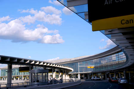 Airport terminal with cars outside and bright blue sky