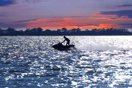 Man on jet ski at sunset photo