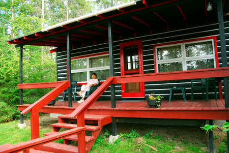 log deck: Woman sitting on a deck of log cabin Stock Photo