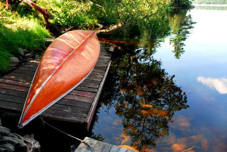 Canoe on wooden dock on a lake photo