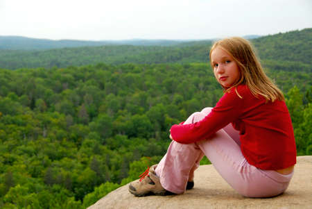 beautiful woodland: Young girl sitting on an edge of a cliff Stock Photo