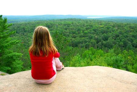 persona sentada: Muchacha joven que se sienta en un borde de un acantilado