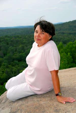 cliff edge: Mature woman sitting on scenic cliff edge