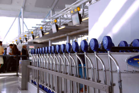 Luggage carts at modern international airport, passengers at check-in counter in the background photo