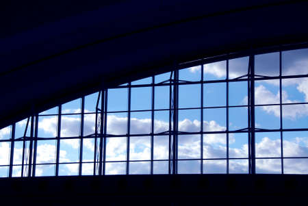 Big window at the moder airport with blue sky and clouds photo