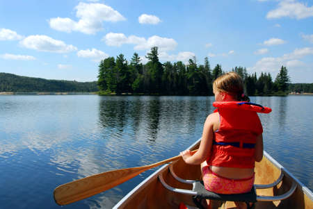 lifejacket: Young girl in canoe paddling on a scenic lake Stock Photo