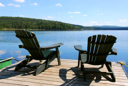 adirondack chair: Two adirondack wooden chairs on dock facing a blue lake with clouds reflections Stock Photo