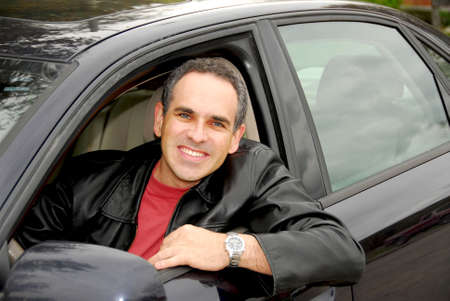 Smiling man looking from a car window photo