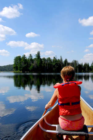 Young girl in canoe paddling on a scenic lake photo