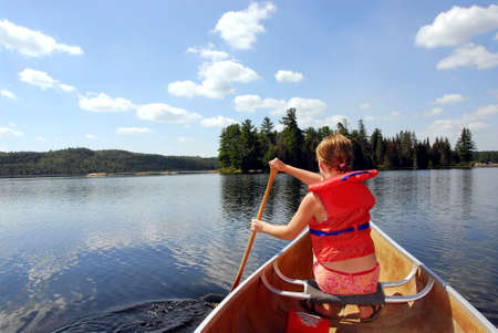 boating: Young girl in canoe paddling on a scenic lake Stock Photo