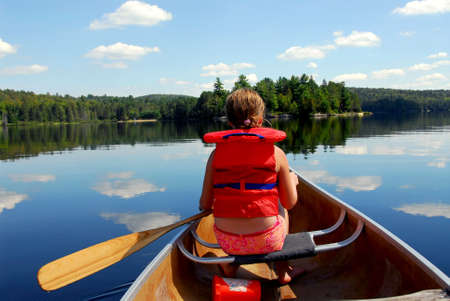 summer girl: Young girl in canoe paddling on a scenic lake Stock Photo