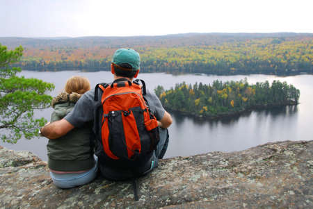 cliff edge: Parent and child sitting on cliff edge enjoying scenic view Stock Photo
