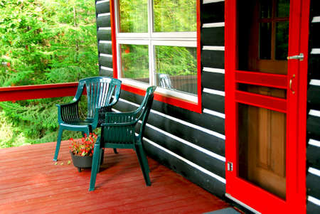 Deck of a log cottage in pine forest photo