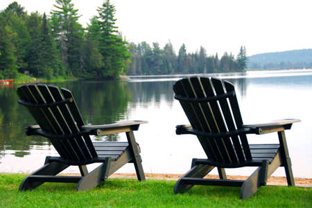 adirondack chair: Two wooden chairs on a lake shore in the evening